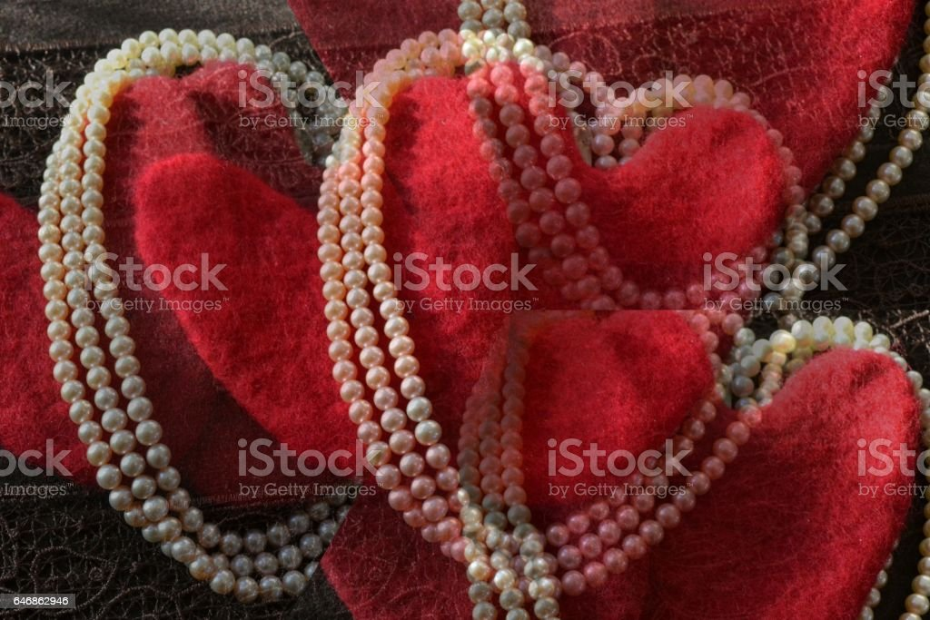 pattern of white pearls and red felted wool stock photo