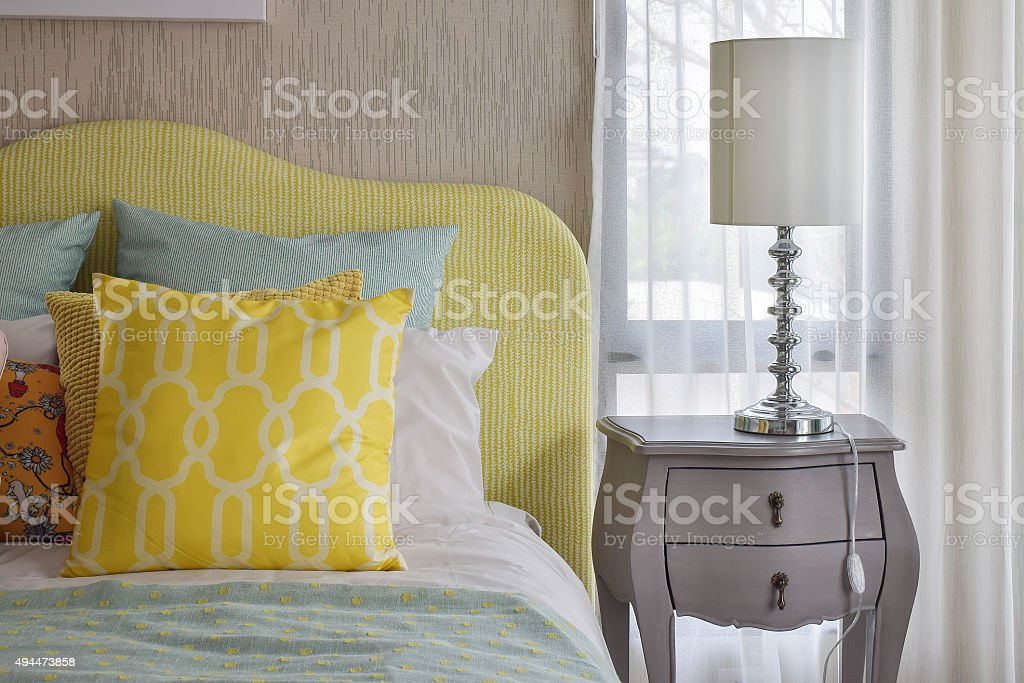 pattern pillows on classic style bed and reading lamp stock photo
