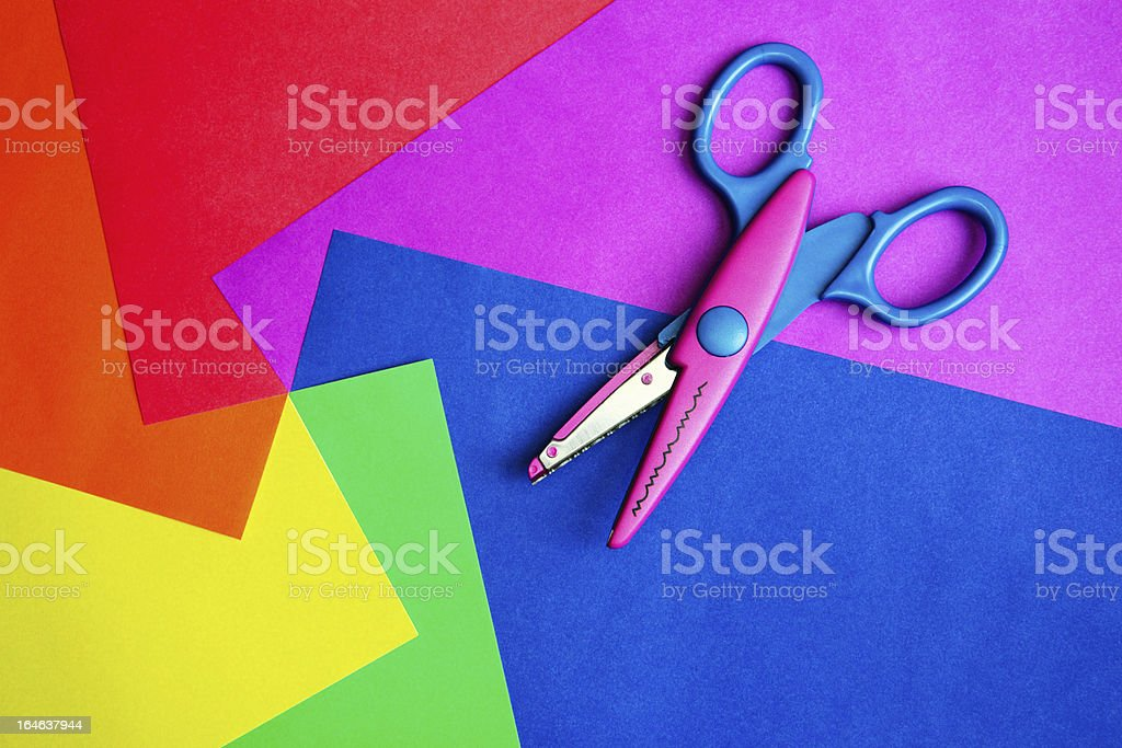 Pattern scissors amongst colorful pieces of rainbow paper stock photo
