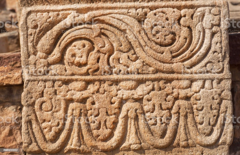 Patterned design of stone relief on wall of 7th century temple in Pattadakal, India. UNESCO World Heritage site stock photo