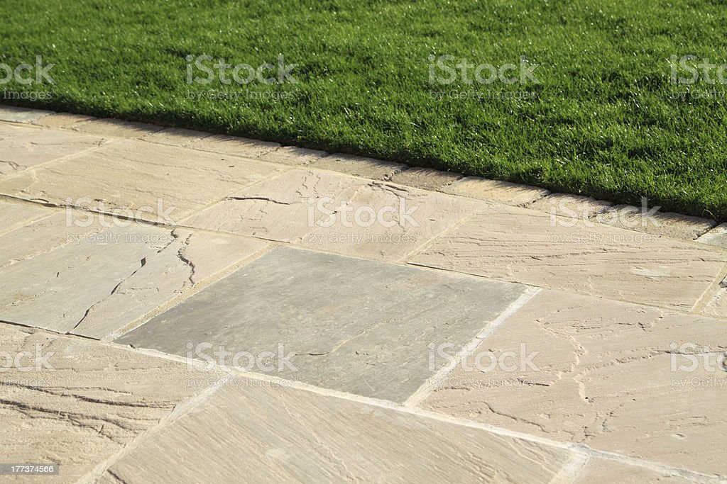 Paved garden patio with grass lawn stock photo
