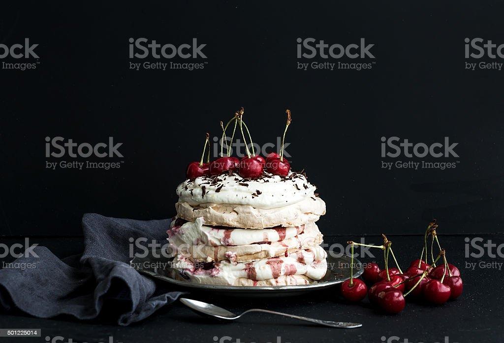 Pavlova cake with fresh cherry, cheese cream and chocolate chips stock photo