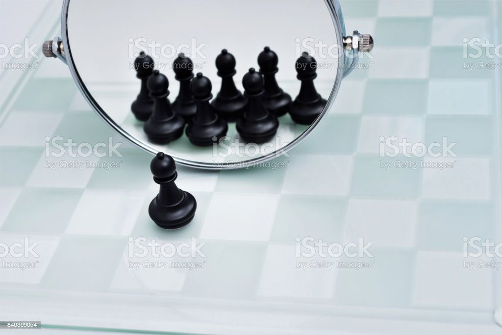 A pawn looking in the mirror stock photo
