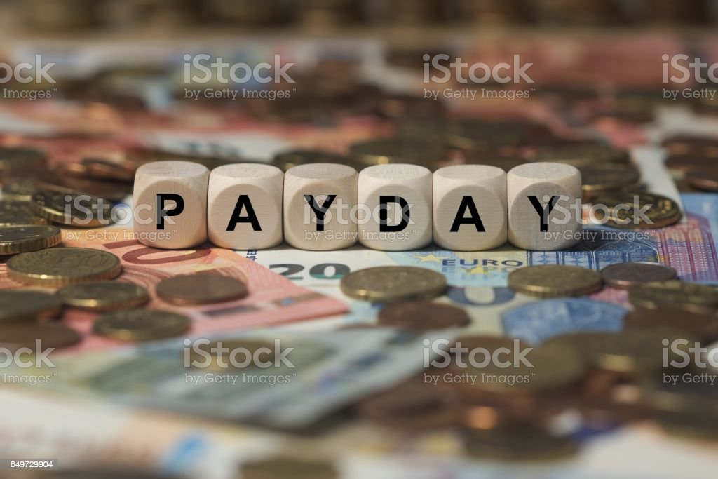 payday - cube with letters, money sector terms - sign with wooden cubes stock photo