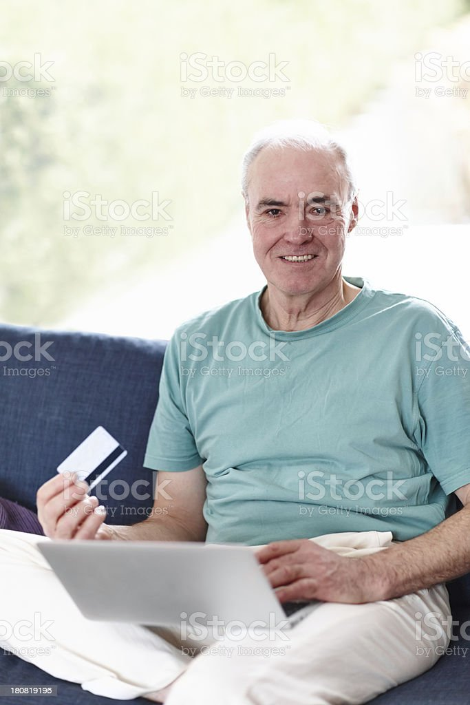Paying bills from the comfort of his couch royalty-free stock photo