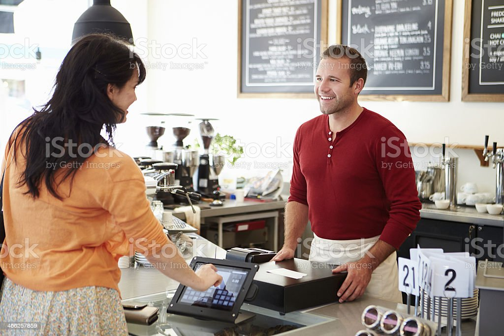 Paying customer with touchscreen monitor stock photo