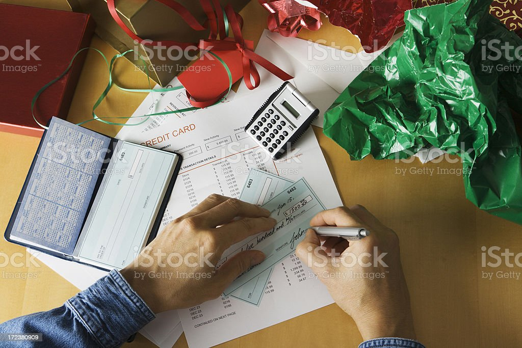 Paying for Christmas—Hands Writing Check with Calculator and Wrapping royalty-free stock photo