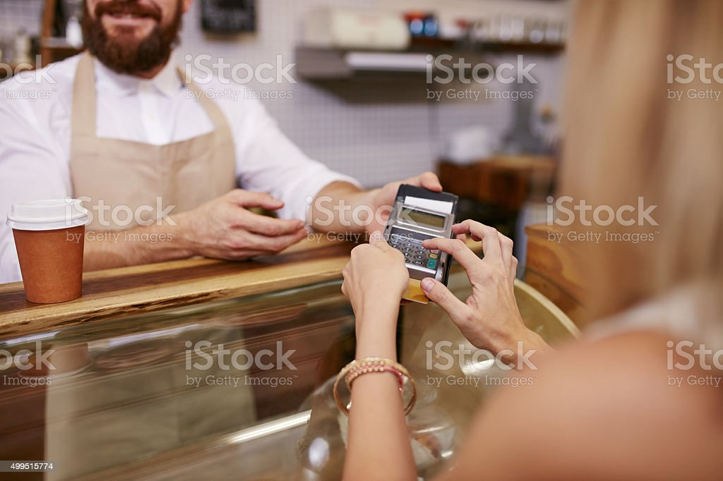 Paying for coffee by credit card reader stock photo
