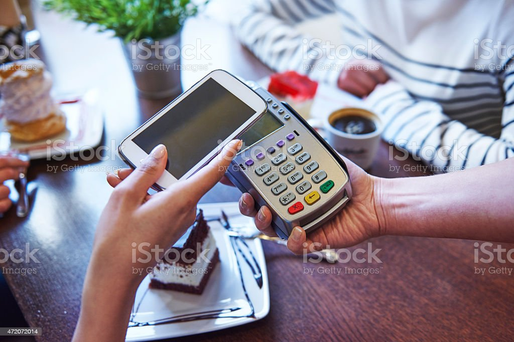 Paying for coffee by mobile phone stock photo