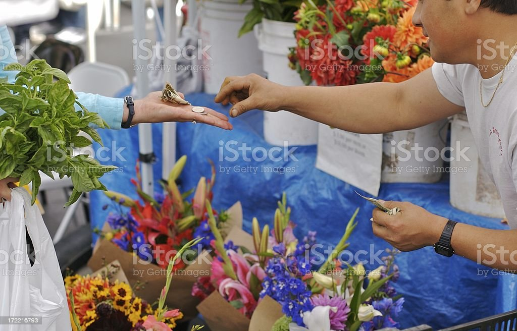 Paying for fresh basil at the farmers market royalty-free stock photo