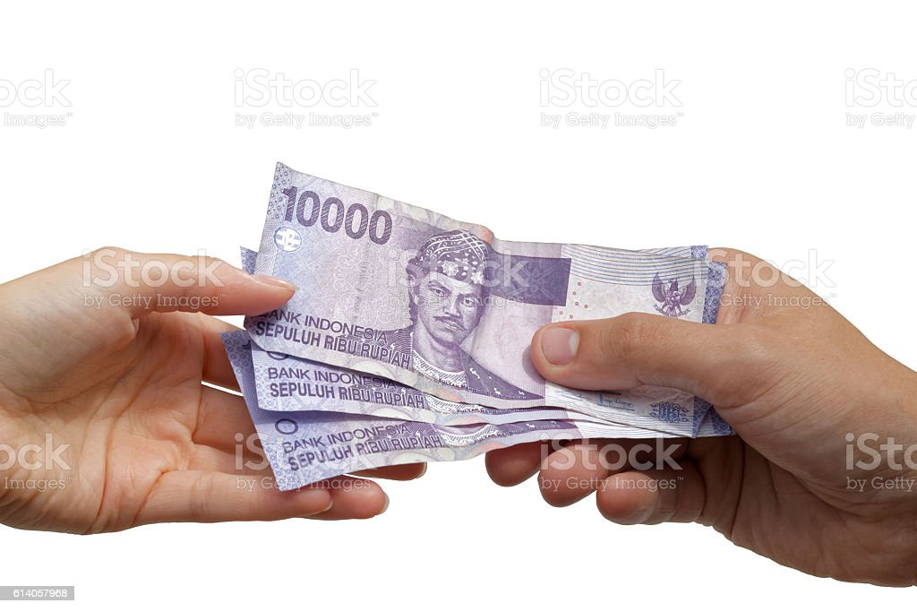 Paying - hand giving Indonesian rupiah banknotes to another hand stock photo