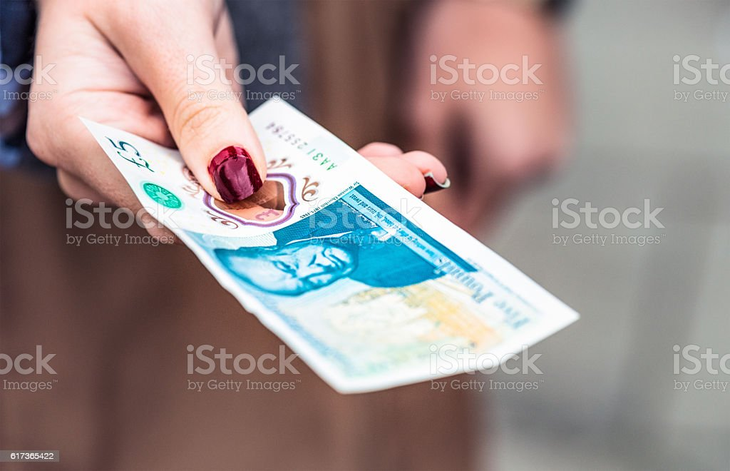 Paying with a new British £5 polymer banknote stock photo