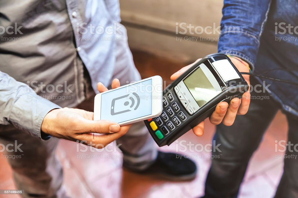 Paying with a smart phone using NFC technology stock photo