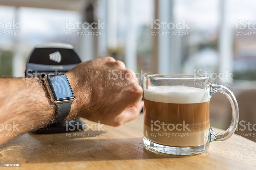 DSLR picture of a human hand paying at coffee shop with a smart watch...