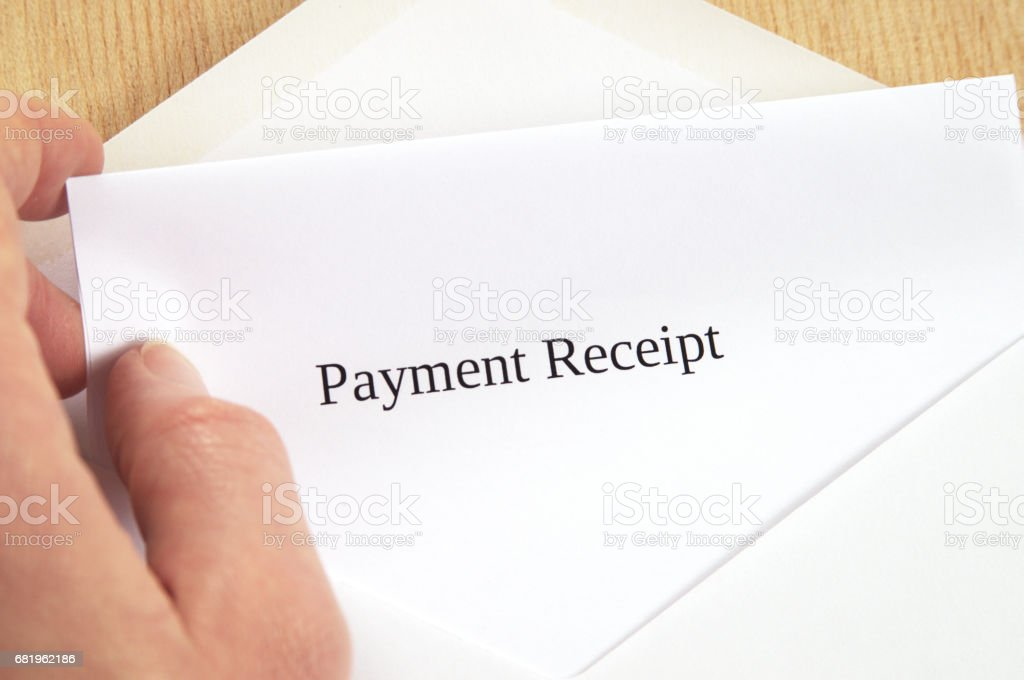 Payment Receipt printed on white paper and envelope, hand holding it, wooden background stock photo