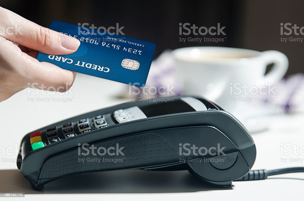 Payment terminal in the restaurant. Coffee in the background stock photo