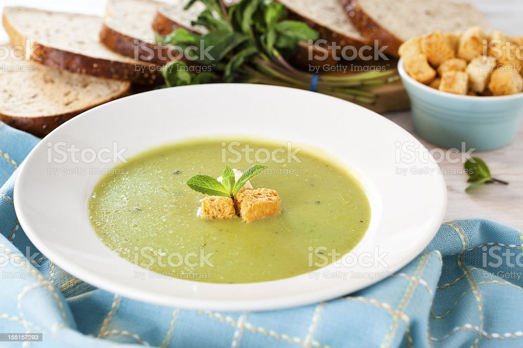 Pea and mint soup with basil and croutons stock photo