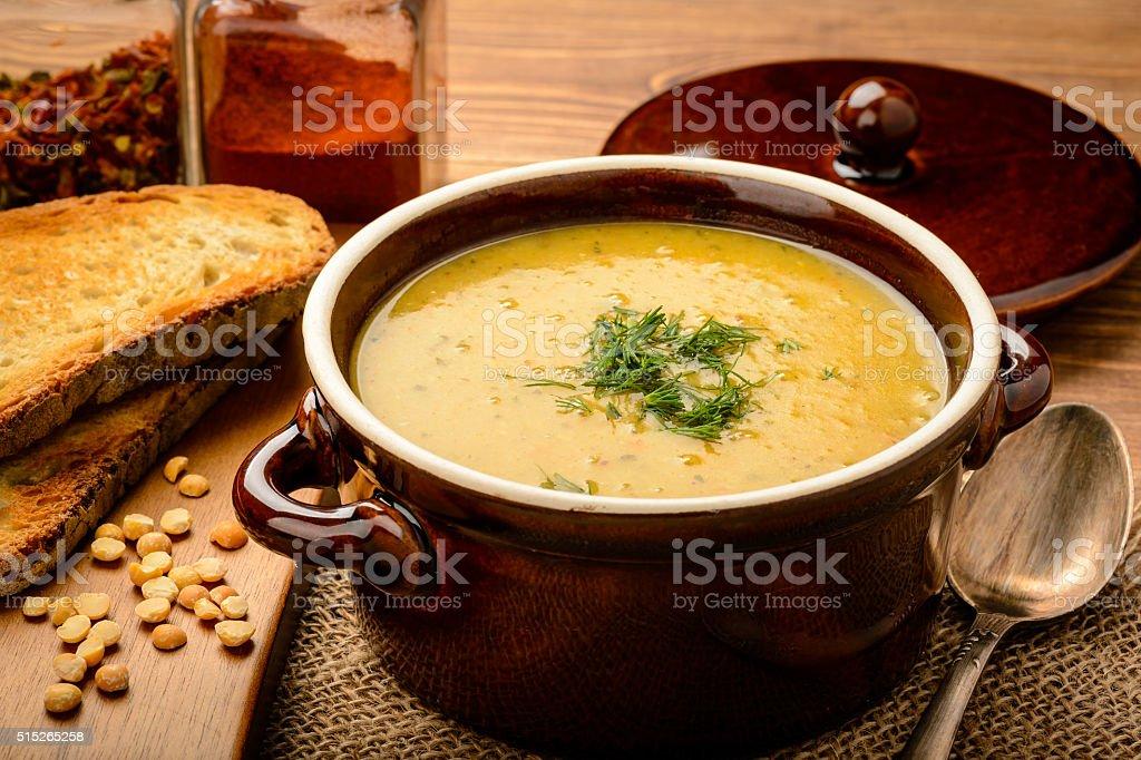 Pea cream soup in brown ceramic pot. stock photo