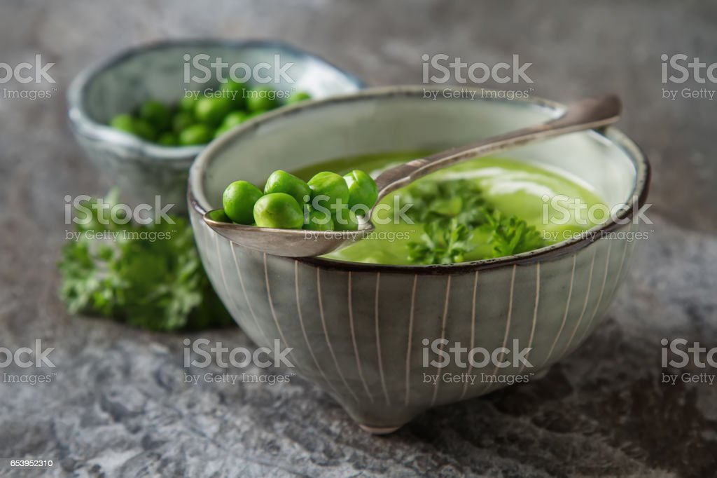 Pea soup puree in an old plate with parsley decoration. Stone sl stock photo