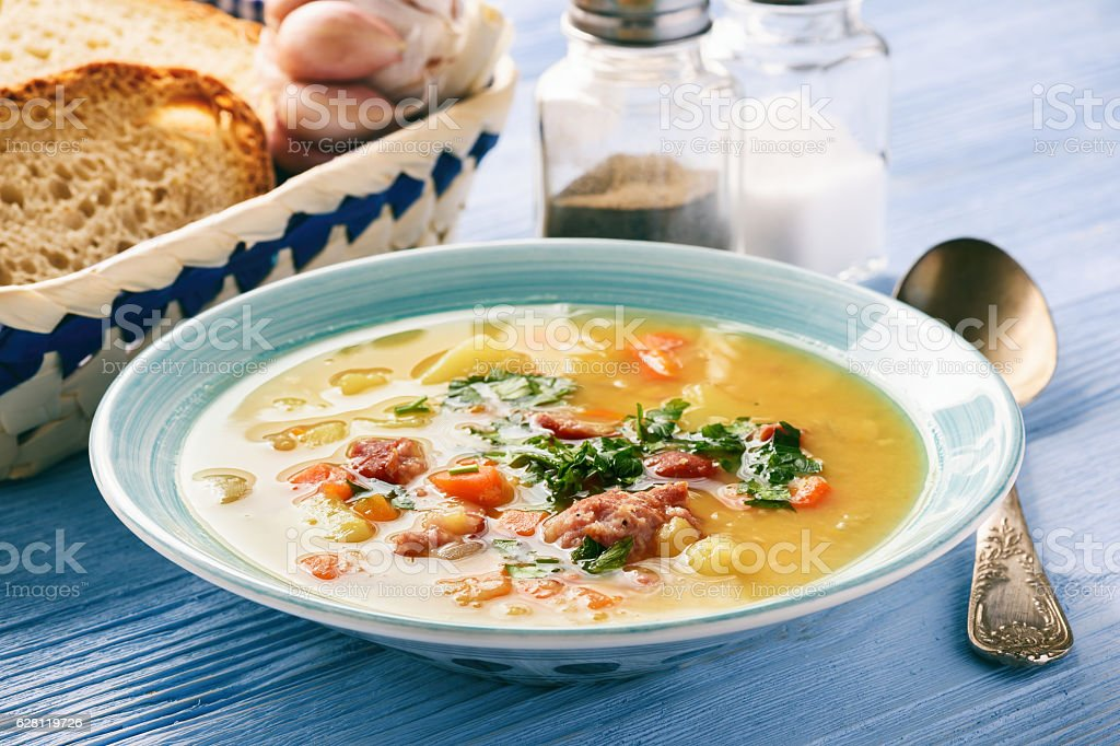Pea soup with smoked sausage on blue wooden background. stock photo