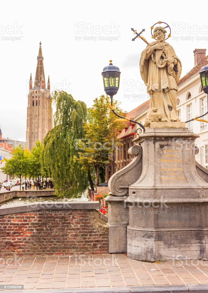 Peace of mind moment off the busy tourist crowd at Sanctus Joannes Nepomucenus statue, Bruges, Belgium, Europe. stock photo