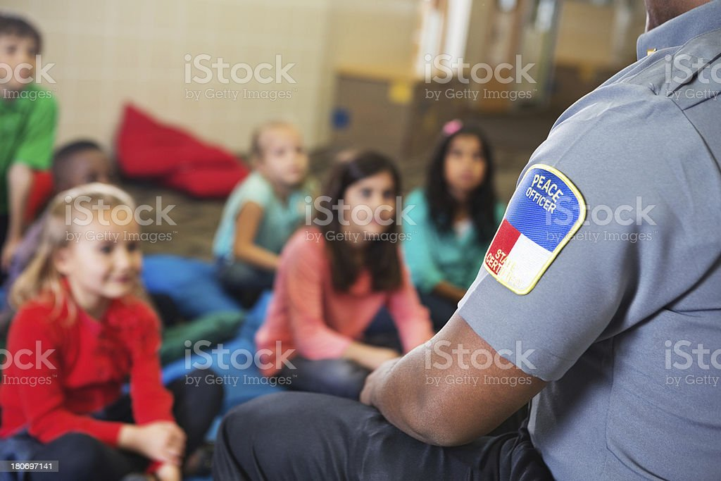 peace officer teaching children about something royalty-free stock photo