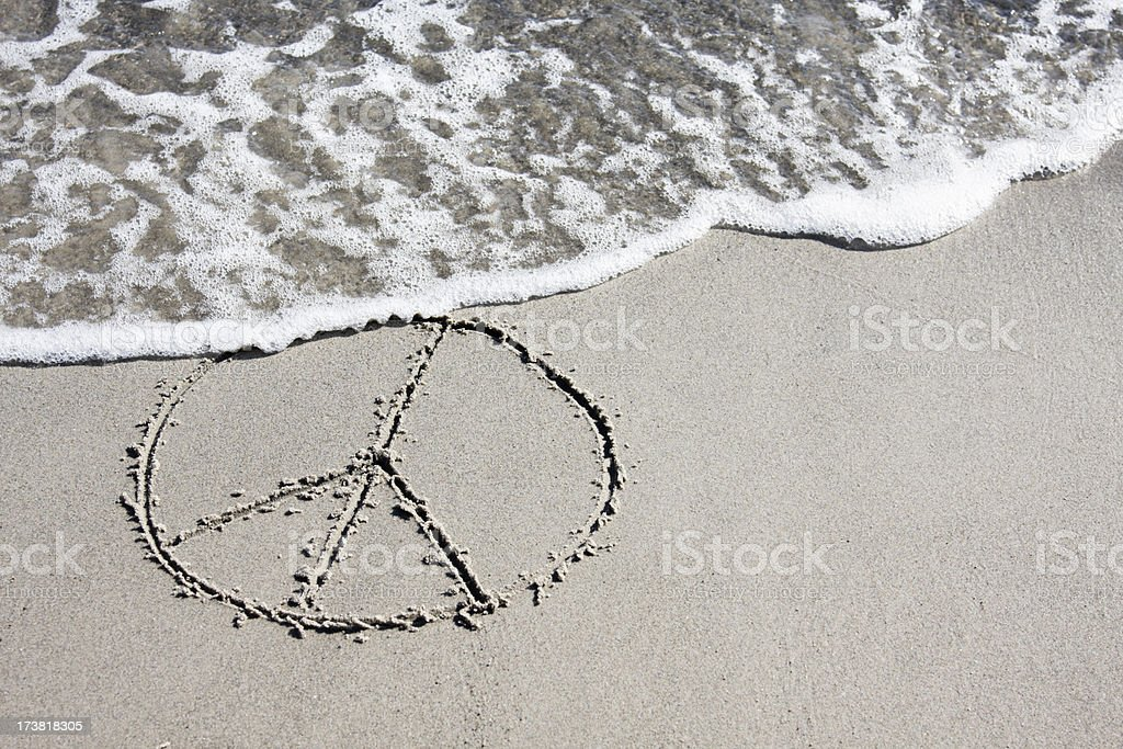 Peace symbol being washed away on the beach. royalty-free stock photo