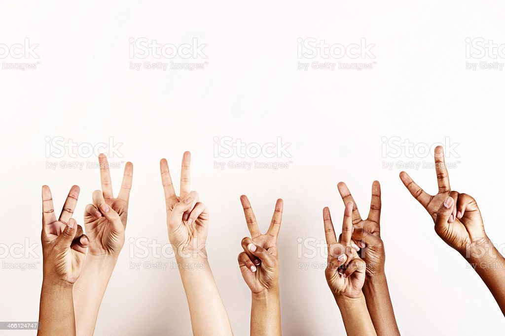 Peace to all! Seven hands giving V-sign stock photo