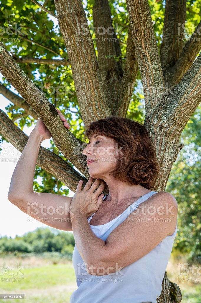 peaceful 50s woman under tree for reinsurance and family roots stock photo
