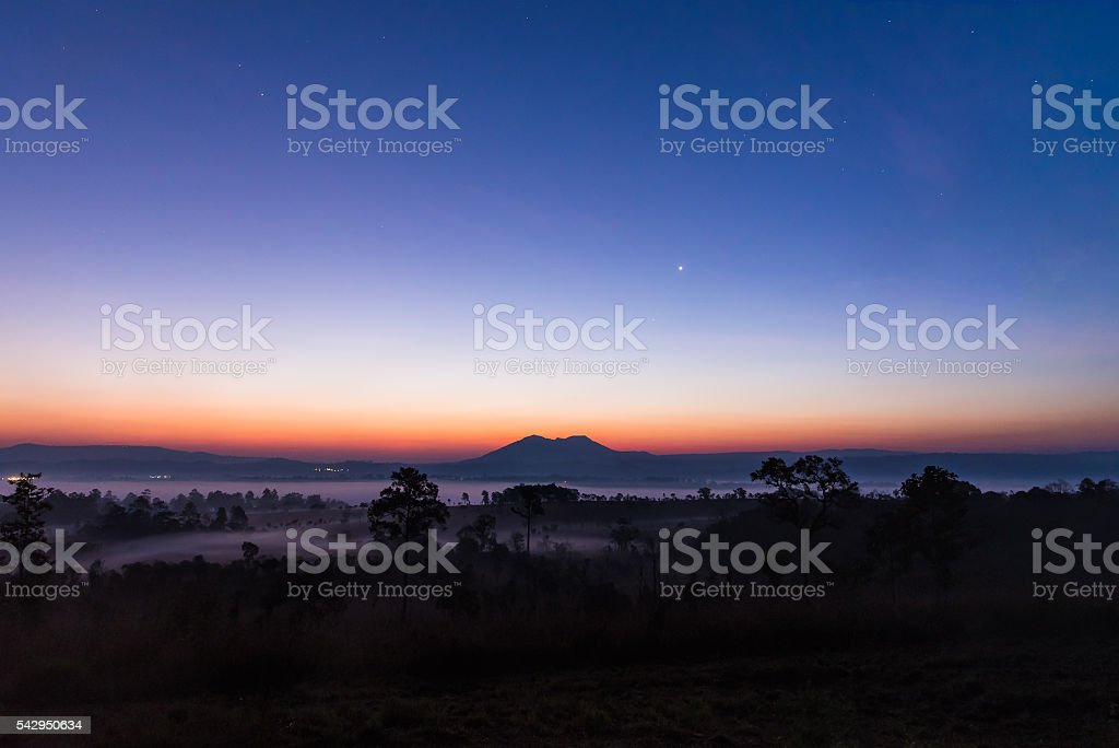 Peaceful early morning dawn sky over mountain and forest. stock photo