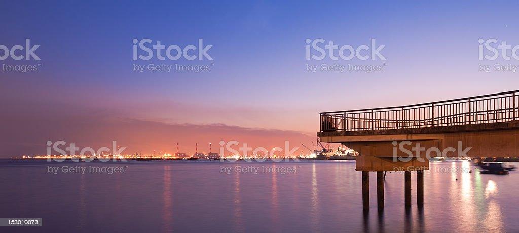 Peaceful jetty overlooking faraway industrial island stock photo