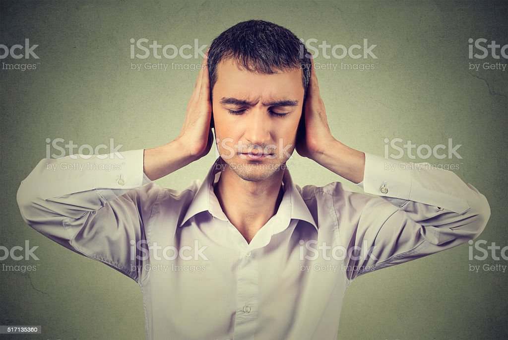 peaceful looking relaxed, young man covering his ears stock photo