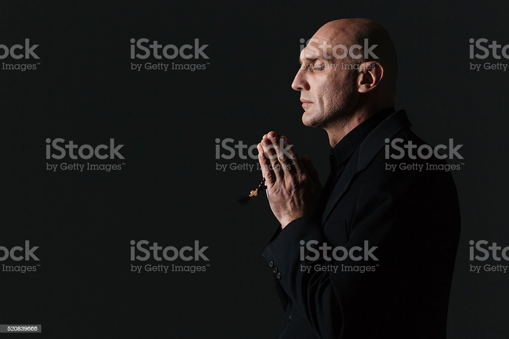 Peaceful man with closed eyes standing and praying stock photo