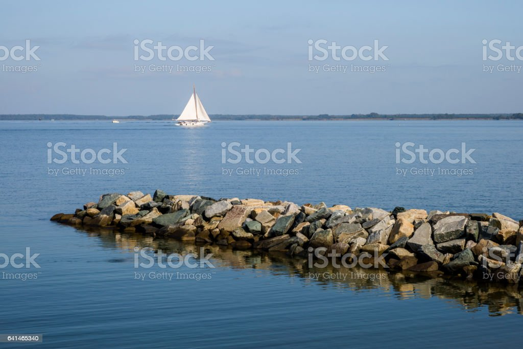 Peaceful Morning--Calm Water, Stone Jetty, Skipjack Sailing Ship stock photo