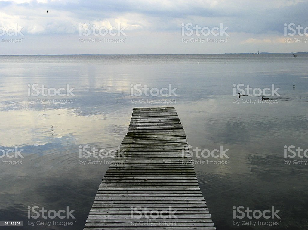 Peaceful old wooden bridge, sea and sky in Denmark royalty-free stock photo