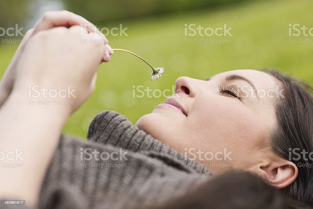 Peaceful pretty woman holding and smelling a daisy royalty-free stock photo