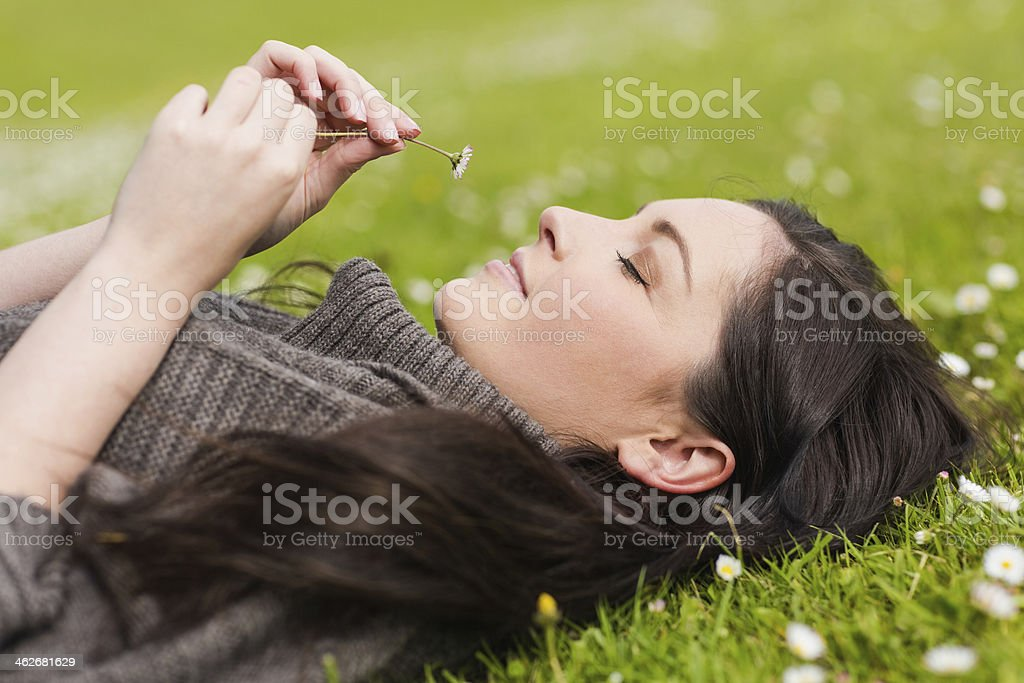 Peaceful pretty woman holding  daisy while lying on the grass royalty-free stock photo