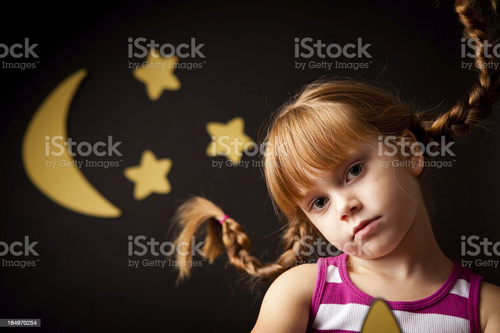 Peaceful Red-Haired Girl with Upward Braids Under Night Sky stock photo