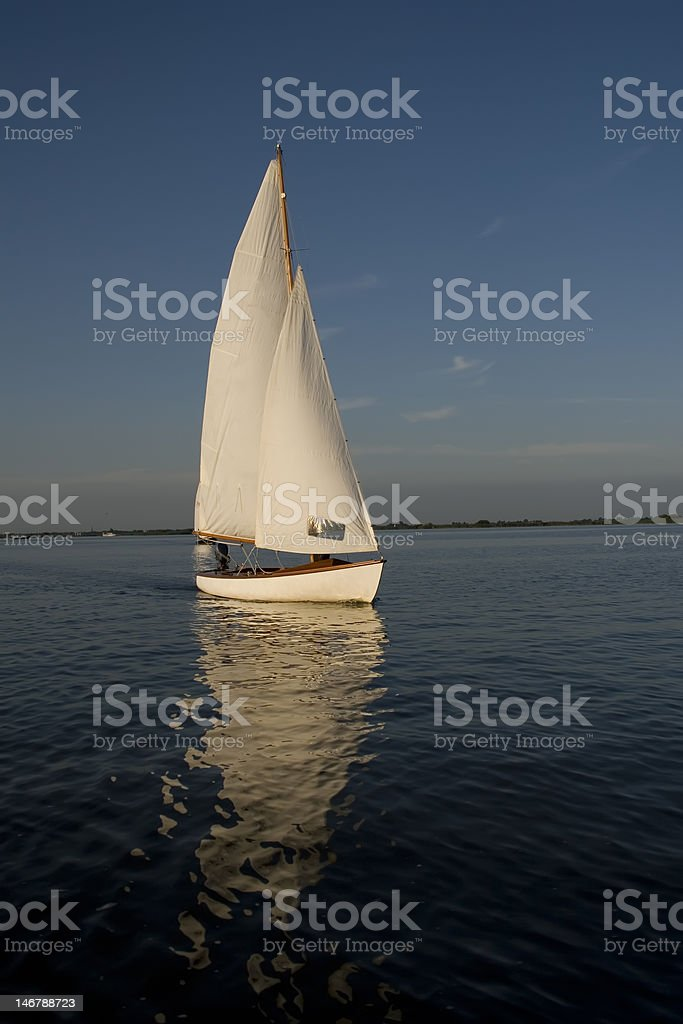 peaceful scene of a white sailing boat in blue water royalty-free stock photo
