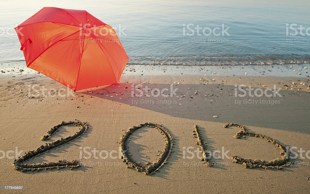 Peaceful seashore with 2013 drawn on  sand stock photo