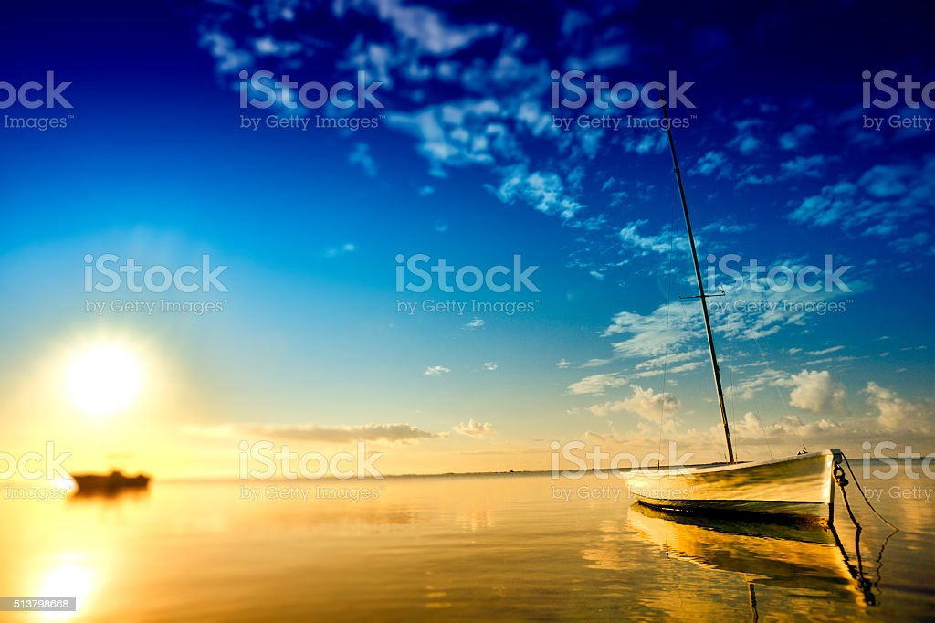 Peacefully anchored sailing boat in Mauritian dawn stock photo