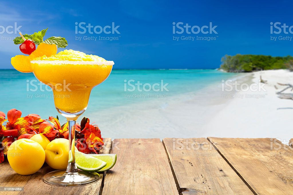Peach daiquiri on wood table against tropical beach background stock photo