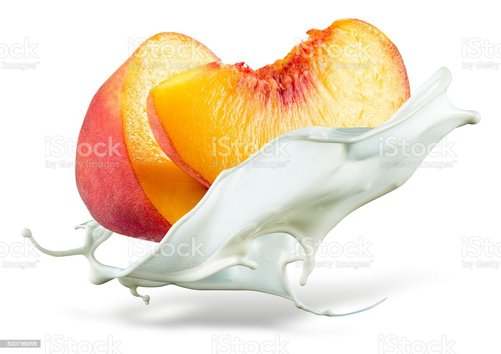 Peach is falling into milk. Splash isolated on white background stock photo