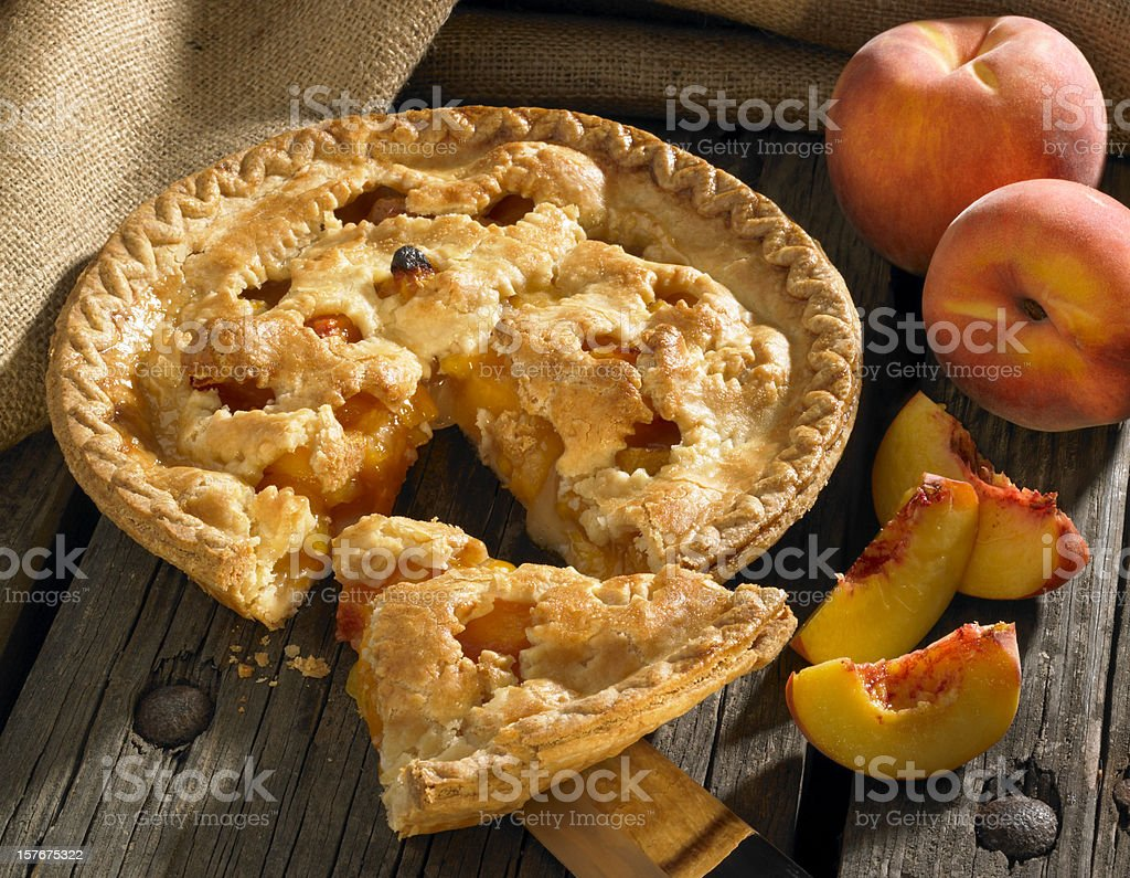 Peach pie on wood rustic background with peaches stock photo