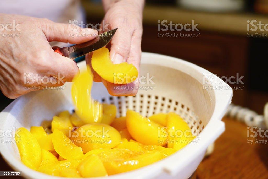 peach slices in a plastic bowl stock photo