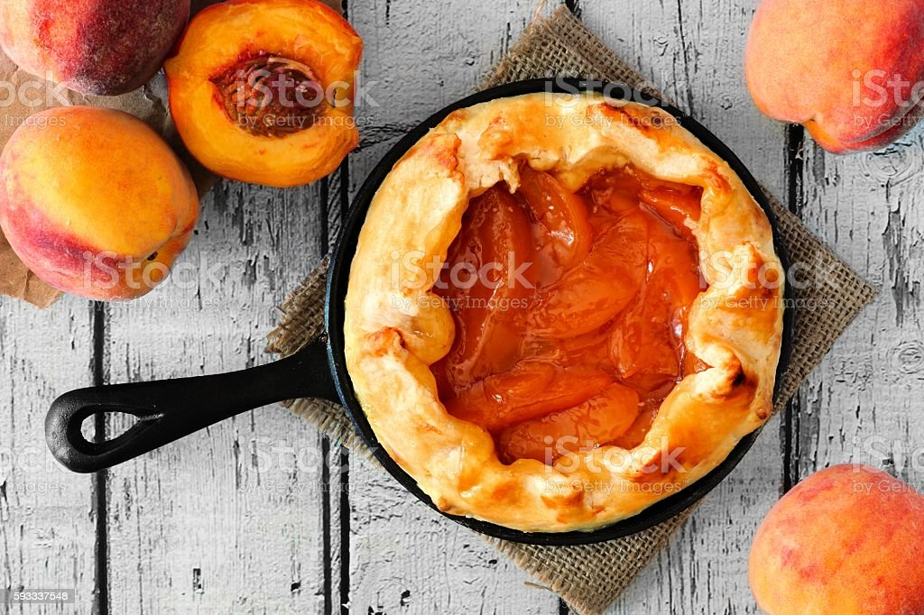 Peach tart in cast iron skillet, overhead on white wood stock photo