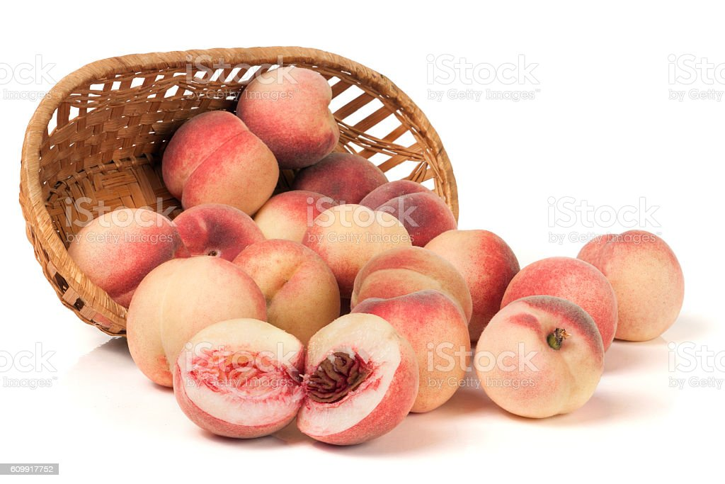 peaches in a wicker basket isolated on white background stock photo
