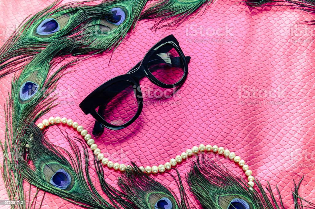 Peacock feathers on a bright pink background with sunglasses stock photo