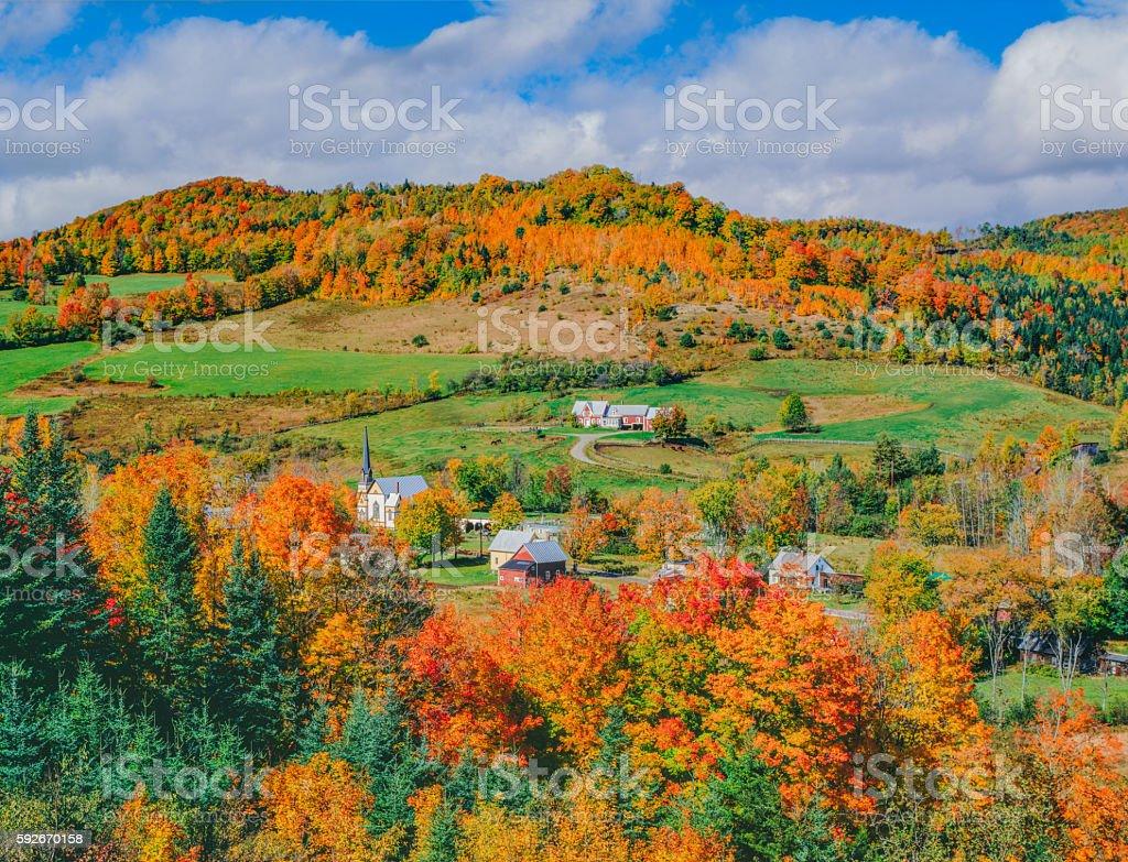 Peak autumn sugar maples with village in Vermont stock photo