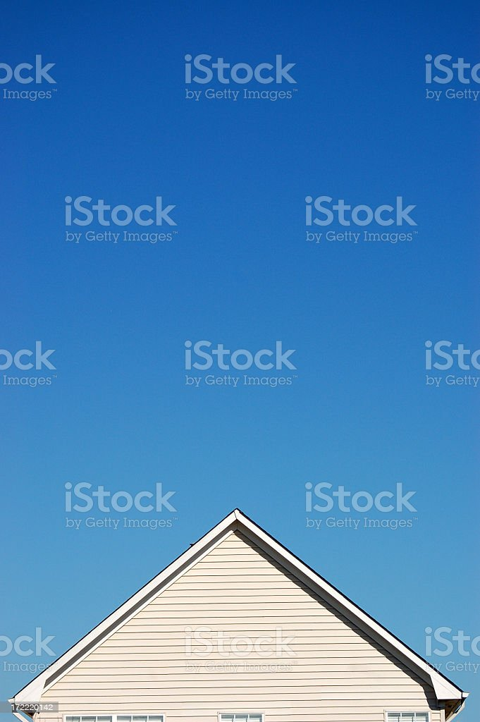 Peak of a house against a clear blue sky stock photo